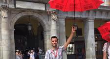 guía sujetando el paraguas rojo de sandemans en el punto de encuentro de la plaza mayor